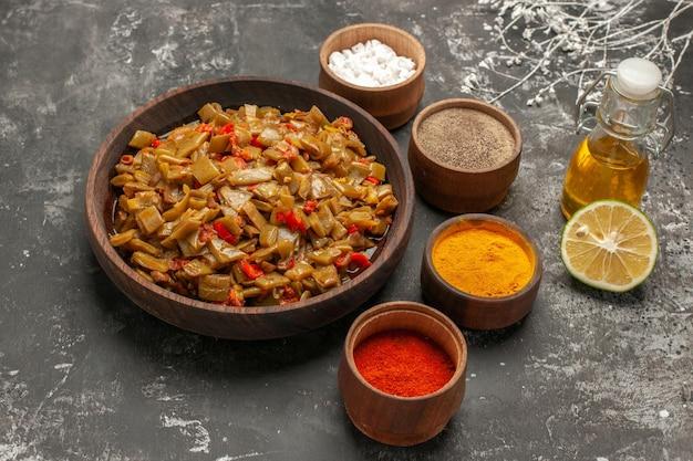 暗いテーブルの上のスパイスボトルのオイルと半分のライムの4つのボウルの横にある食欲をそそるサヤインゲンとトマトの食欲をそそる皿プレートの側面拡大図