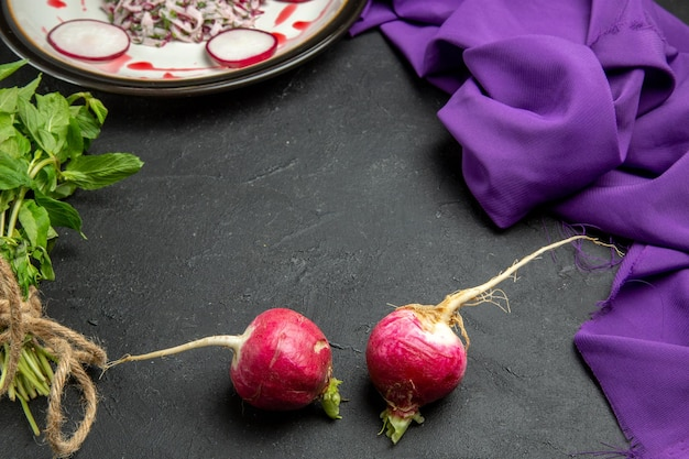 Side close-up view an appetizing dish white plate of sauce and radish herbs and purple tablecloth
