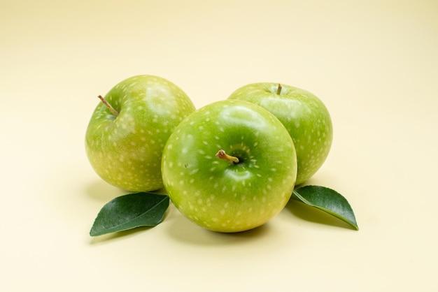 Vista ravvicinata laterale mele le appetitose mele verdi con foglie sulla superficie bianca