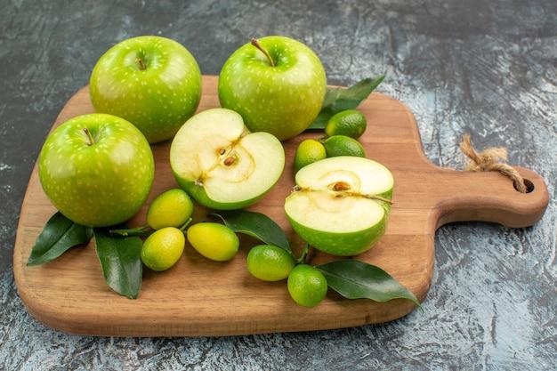 側面のクローズアップビューリンゴ柑橘系の果物ボードに葉を持つリンゴ