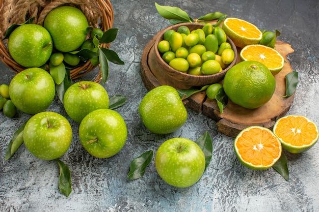 側面のクローズアップビューリンゴの葉とリンゴのボードバスケット上の柑橘系の果物
