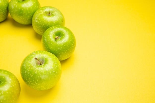 Vista ravvicinata laterale mele mele verdi sono disposte in un cerchio sul tavolo