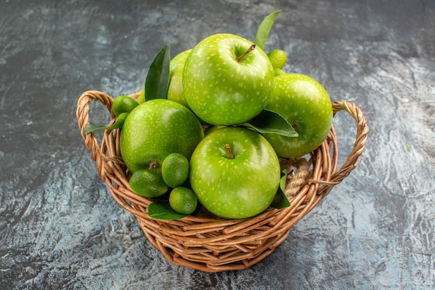 Side close-up view apples green apples with leaves citrus fruits in the basket