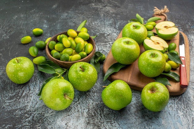 側面のクローズアップビューりんご柑橘系の果物のボードボウルに葉を持つ青リンゴ