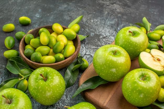 側面のクローズアップビューリンゴボード上の葉を持つ食欲をそそるリンゴ柑橘系の果物