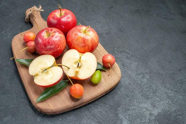 側面のクローズアップビューは、木の板に食欲をそそる柑橘系の果物のサクランボとリンゴをリンゴ
