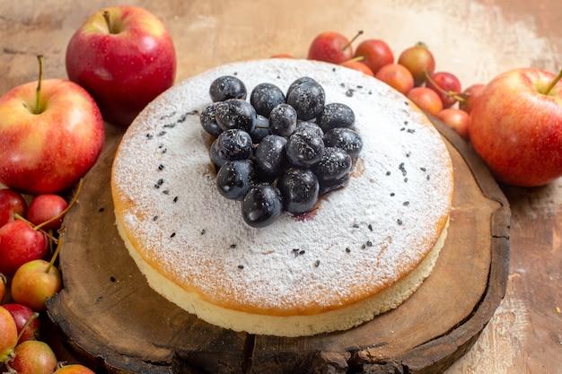 Vista ravvicinata laterale bacche una torta appetitosa con uva nera sulle mele e sui frutti di bosco