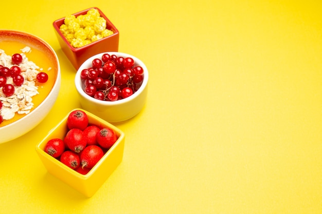Side close-up view berries berries oatmeal yellow candies in the bowls