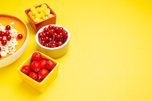 Вид сбоку крупным планом ягоды, ягоды, овсяные хлопья, желтые конфеты в мисках