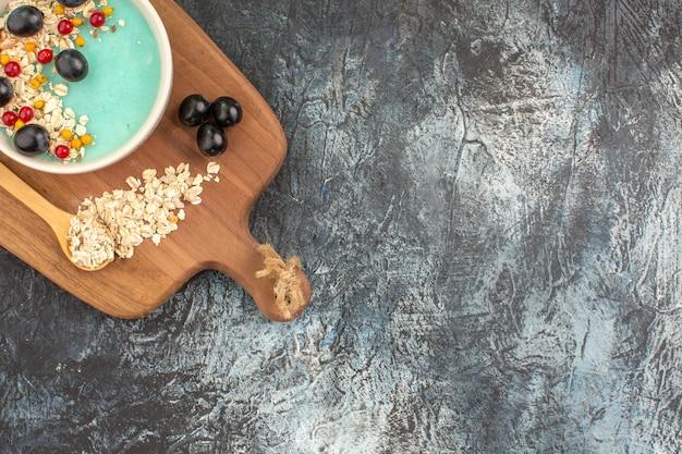 Vista ravvicinata laterale bacche uva nera ribes rosso cucchiaio di farina d'avena sul bordo