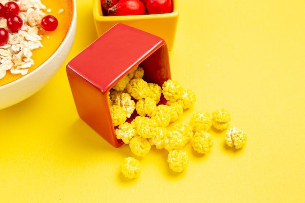 Vista ravvicinata laterale bacche ciotole di caramelle bacche colorate sul tavolo