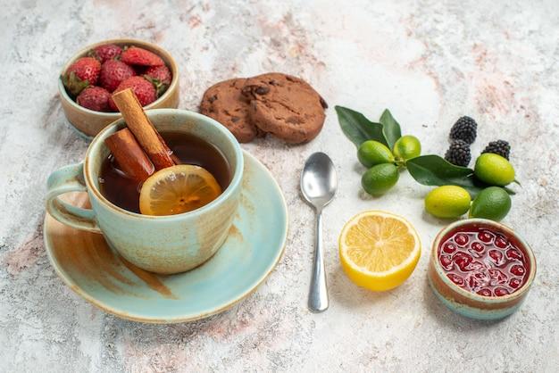 측면 클로즈업 보기 베리 베리 그릇 초콜릿 쿠키 감귤류 과일 석류 레몬 스푼 테이블에 레몬이 든 차 한 잔