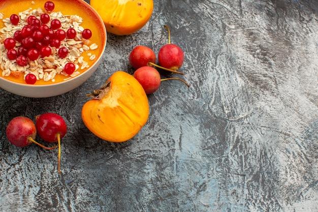 Вид сбоку крупным планом ягоды вишня миска из красной смородины аппетитная хурма