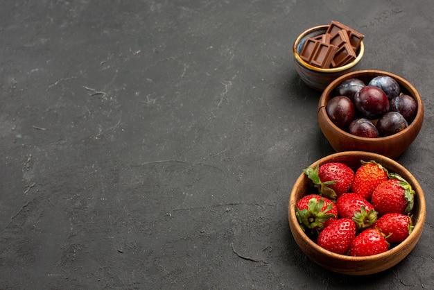 Боковой вид крупным планом ягоды, шоколад, клубника и ягоды в деревянных мисках на темном столе
