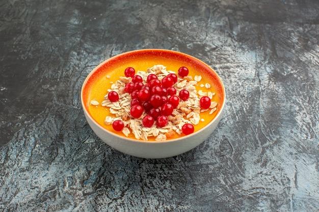 側面のクローズアップビューは、灰色のテーブルに食欲をそそる赤スグリのオレンジボウルをベリーします