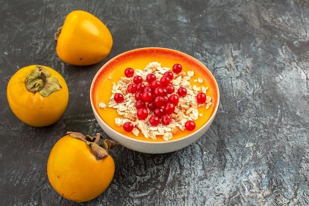側面のクローズアップビューは、オレンジボウルに3つの食欲をそそる柿の果実をベリーします