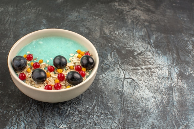 Side close-up view berries white plate of the appetizing red currants grapes on the table