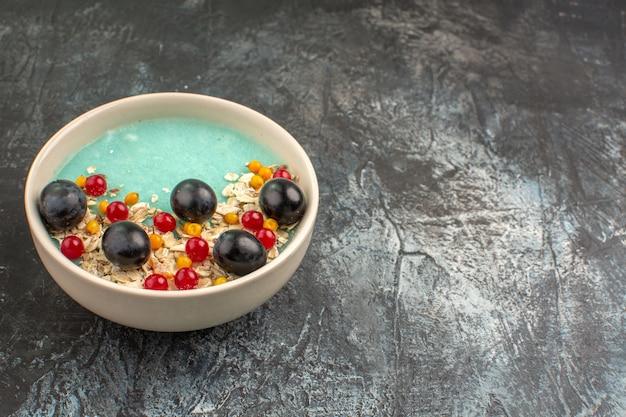 側面のクローズアップビューは、テーブルの上の食欲をそそる赤スグリのブドウの白いプレートをベリーします