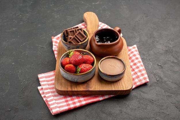 Vista ravvicinata laterale ciotole a bordo frutti di bosco e crema al cioccolato in ciotole sul tagliere di legno sulla tovaglia a scacchi bianco-rosa sul tavolo scuro