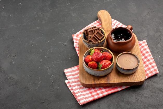 暗いテーブルの右側にあるピンクホワイトの市松模様のテーブルクロスにある木製のまな板にチョコレートクリームとイチゴのボウルの側面のクローズアップビューボウル