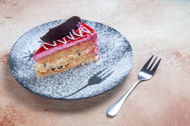 側面のクローズアップビューケーキプレートフォークにチョコレートと食欲をそそるケーキ