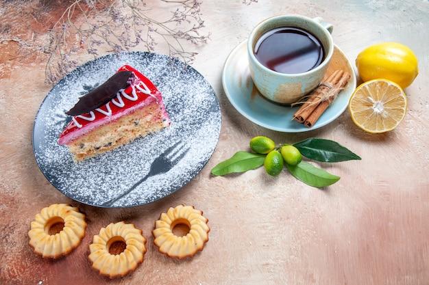 Vista ravvicinata laterale una torta una torta appetitosa biscotti una tazza di tè cannella limone