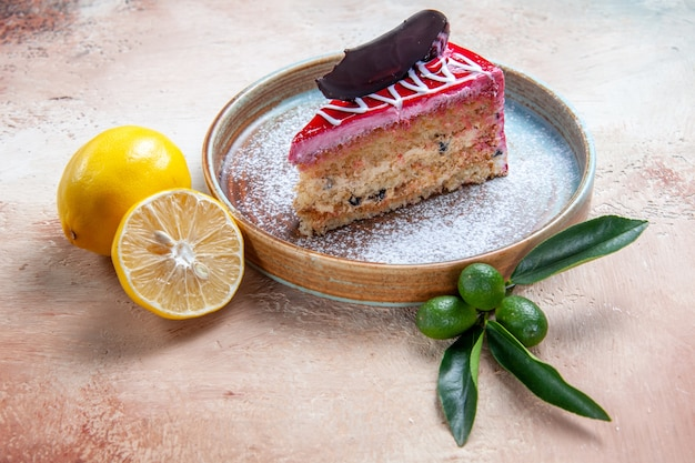 Side close-up view a cake an appetizing cake with chocolate and sauces on the plate citrus fruits