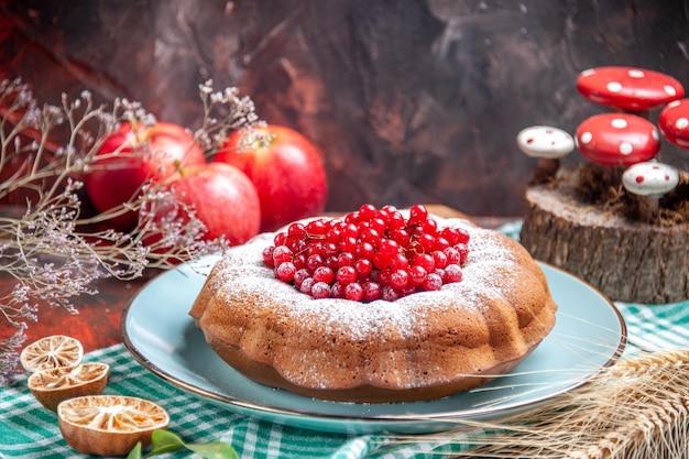 Vista ravvicinata laterale una torta una torta appetitosa con ribes rosso sulle mele della tovaglia bianco-blu