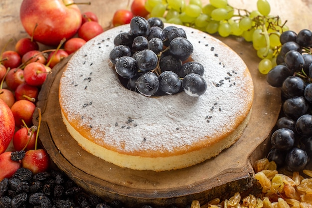 Vista ravvicinata laterale una torta una torta appetitosa sulla tavola di legno uva uva passa mele ciliegia