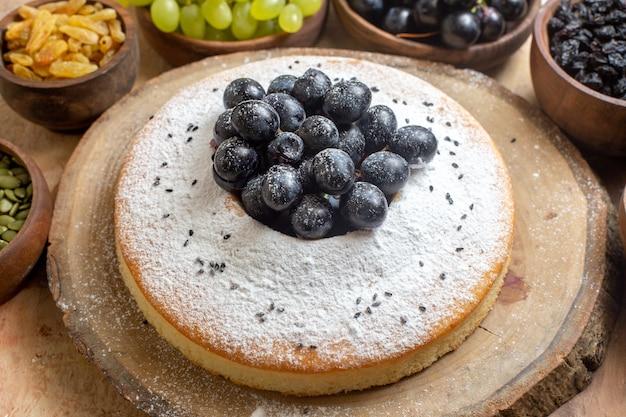 Vista ravvicinata laterale una torta una torta sul bordo ciotole di uva semi di zucca uvetta