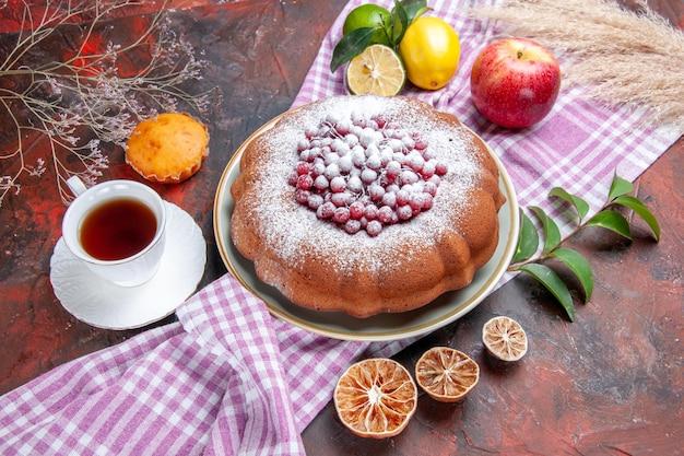Vista ravvicinata laterale una torta una torta una tazza di tè cupcake mela limoni con foglie sulla tovaglia