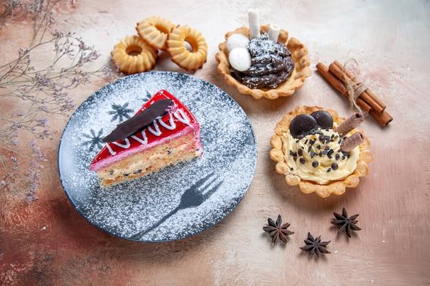 Vista ravvicinata laterale una torta una torta cupcakes cannella bastoni taccuino di biscotti all'anice stellato