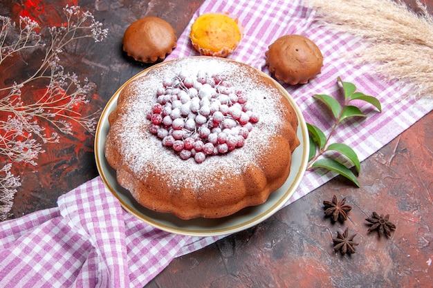 Vista ravvicinata laterale una torta una torta cupcakes lascia sulla tovaglia a quadretti anice stellato