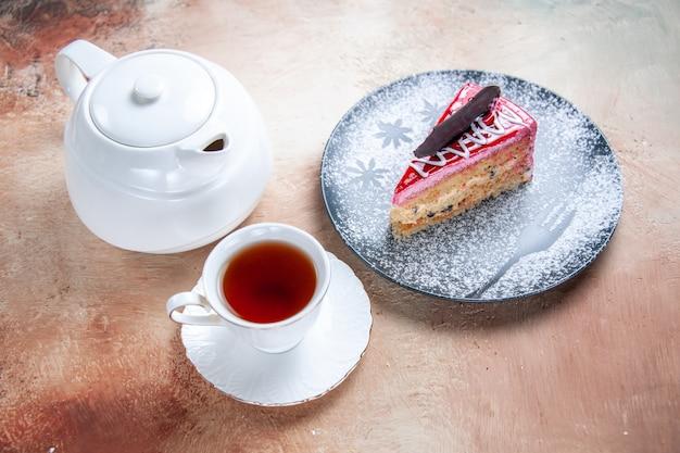 Vista ravvicinata laterale una torta una tazza di tè bianca della teiera della torta