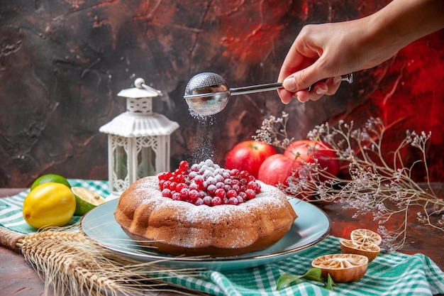 Side close-up view a cake a cake with berries citrus fruits apples spoon in the hand
