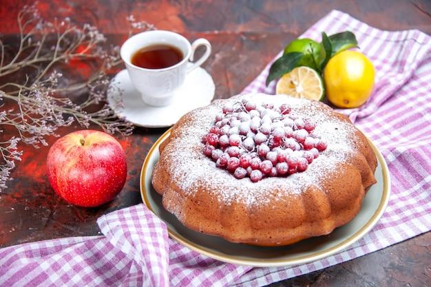Vista ravvicinata laterale una torta una torta con frutti di bosco agrumi sulla tovaglia una tazza di tè