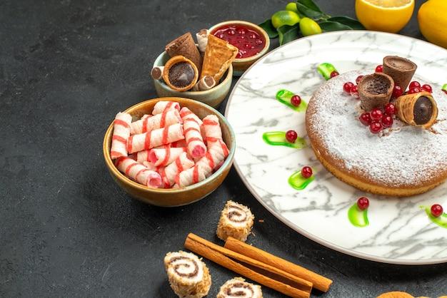 Vista ravvicinata laterale una torta una torta con marmellata di frutti di bosco dolci agrumi cannella biscotti