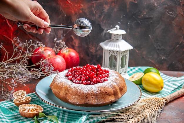 Vista ravvicinata laterale una torta una torta con frutti di bosco limoni sulla tovaglia mele cucchiaio in mano