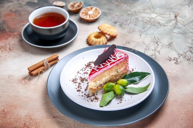 Vista ravvicinata laterale una torta una torta con agrumi al cioccolato una tazza di tè biscotti alla cannella