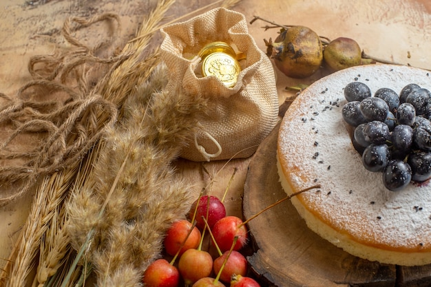 Vista ravvicinata laterale una torta una torta con le spighette di caramelle bacche di uva
