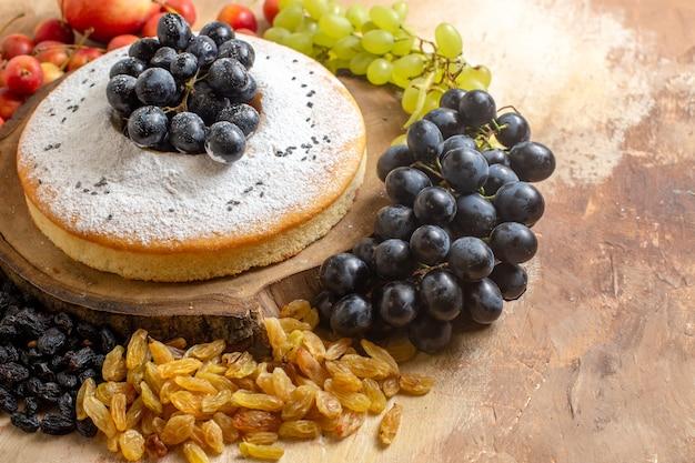 Vista ravvicinata laterale una torta una torta con l'uva sulla tavola di legno uva passa ciliegia mele uva