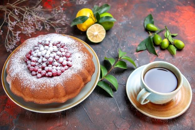 Vista ravvicinata laterale torta una torta con zucchero a velo una tazza di tè agrumi con foglie
