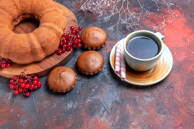Vista ravvicinata laterale torta una torta con ribes rosso sulla tavola cupcakes una tazza di tè con caramelle