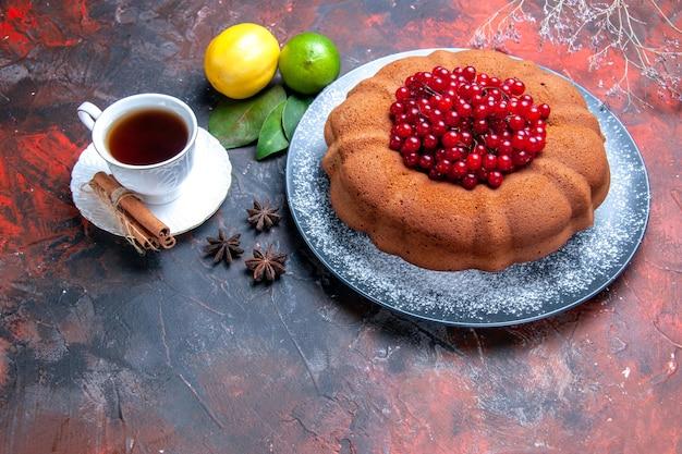 Vista ravvicinata laterale torta torta con ribes rosso sul piatto limone una tazza di tè foglie di anice stellato