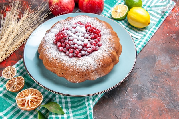 Vista ravvicinata laterale una torta una torta con ribes rosso zucchero a velo limoni mele sulla tovaglia