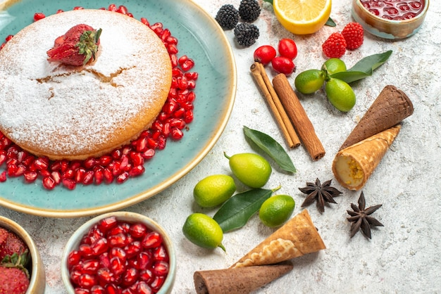 Vista ravvicinata laterale una torta una torta con fragole e marmellata di melograno limone cannella anice stellato