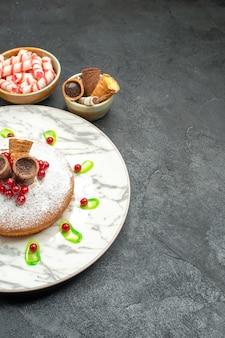 Vista ravvicinata laterale una torta una torta con cialde ribes rosso ciotole di dolci