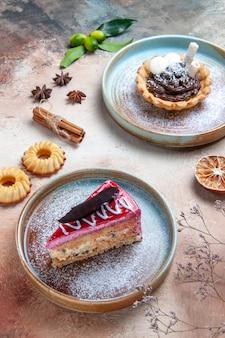 Vista ravvicinata laterale torta agrumi piatto di torta cupcake biscotti cannella