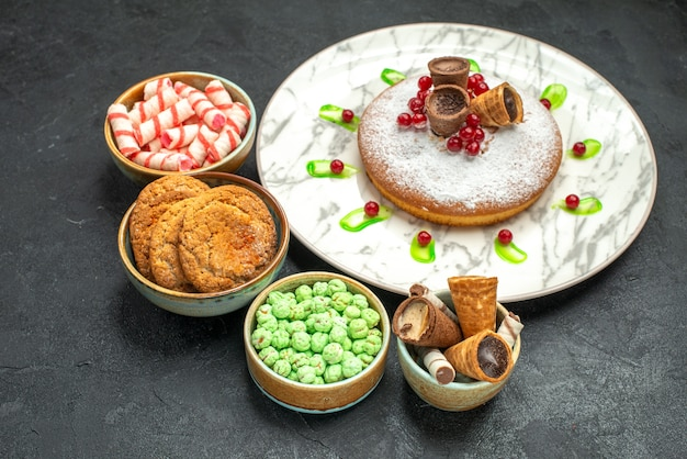 Vista ravvicinata laterale una torta biscotti dolci in ciotole piatto di torta con cialde di frutti di bosco