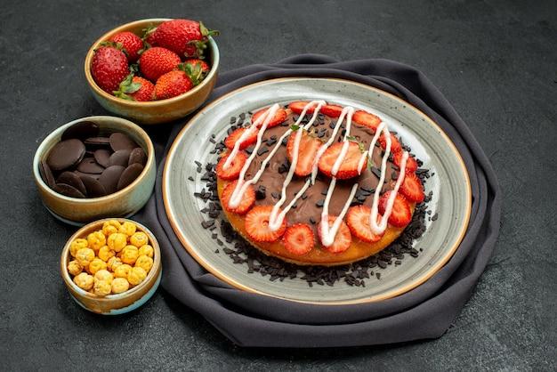 딸기 헤이즐넛과 초콜릿의 식탁보 그릇에 있는 측면 클로즈업 보기 케이크, 검은 탁자에 있는 회색 식탁보에 초콜릿과 딸기가 있는 케이크